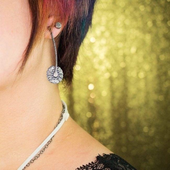 Sterling silver daisy earrings by Popnicute Jewelry on model.