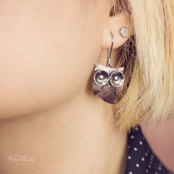 Whimsical owl earrings by Popnicute Jewelry. Small copper dangle earrings with argentium ear wires on model.