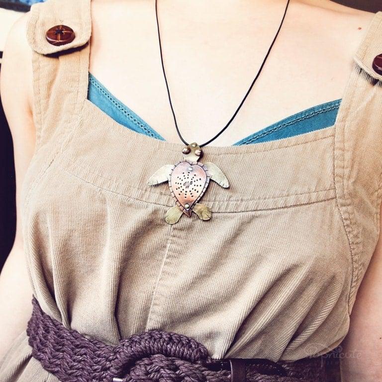 Myrtle Sea Turtle copper brass artisan necklace by Popnicute Jewelry on model. Handmade to order.