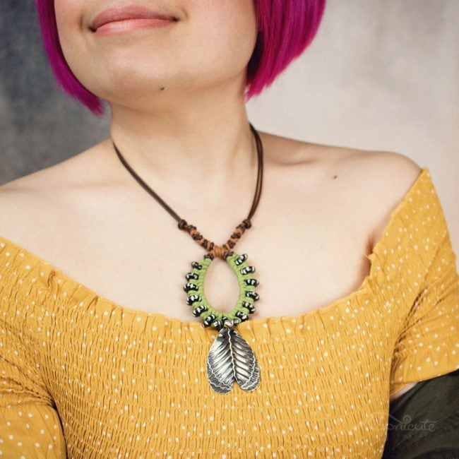 Imperial moth caterpillar necklace by Popnicute Jewelry. On model, short.