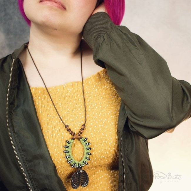 Imperial moth caterpillar necklace by Popnicute Jewelry. On model, long.