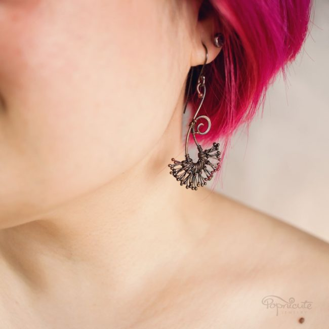 Dandier than the white puff dandelion seeds, these copper dandelion earrings surely will turn heads. They move with you. Swirly design. Handcrafted art jewelry. On model.