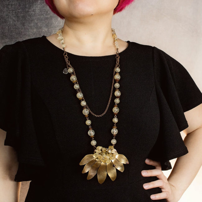 4 in 1 Sunflower necklace with citrine and pinapple quartz by Popnicute Jewelry on model. Brass, copper, and argentium silver.